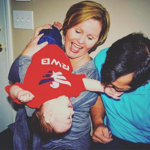 Two white parents playing with a baby