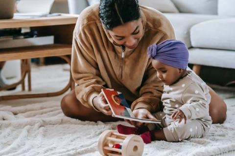 Black mom reading to baby