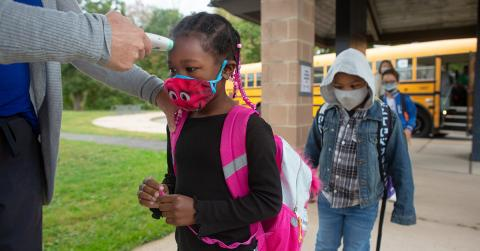 A child gets their temperature checked on the way to school