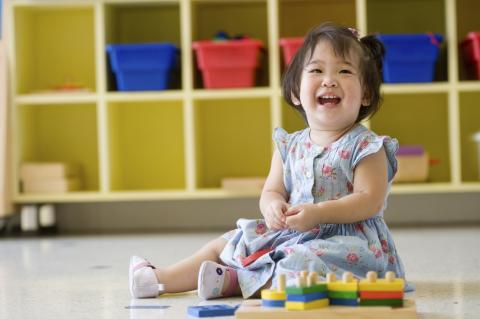 [IMAGE DESCRIPTION: A young child with shoulder length black hair wears a light blue dress, sits on the floor with bright color blocks, and laughs.]