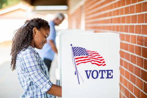 [IMAGE DESCRIPTION: Person with long dark curly hair stands at a voting booth.]