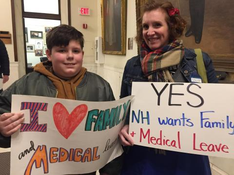 [IMAGE DESCRIPTION: Mother and son look at camera, smiling, holding sign for paid family and medical leave in New Hampshire.]