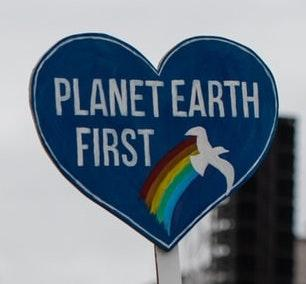 "[IMAGE DESCRIPTION: A photo of a cardboard blue heart that says ""Planet Earth First""]"