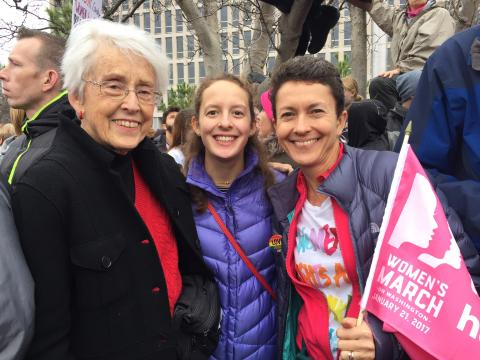 [IMAGE DESCRIPTION: A photo of three people smiling at the camera, one holding a pink flag.]