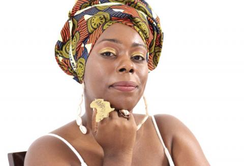 [IMAGE DESCRIPTION: A photo of a person looking at the camera with a slight smile, wearing a colorful headwrap and a matte gold ring in the shape of the African continent.]