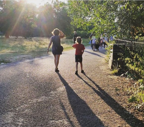 Mother and child walking away from the camera in a park with long shadows behind them