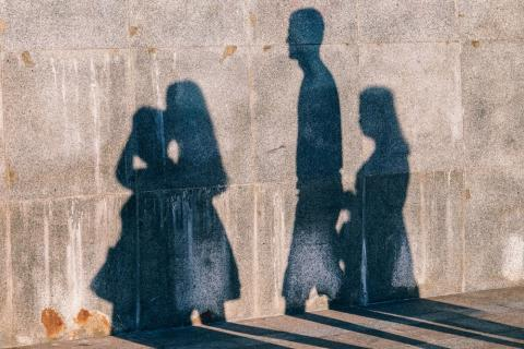 A family's shadows shown on wall. Photo by Igor Ovsyannykov on Unsplash