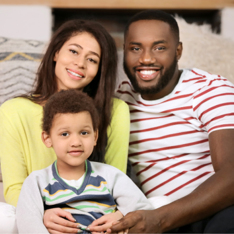 Young parents with brown skin sitting with their son