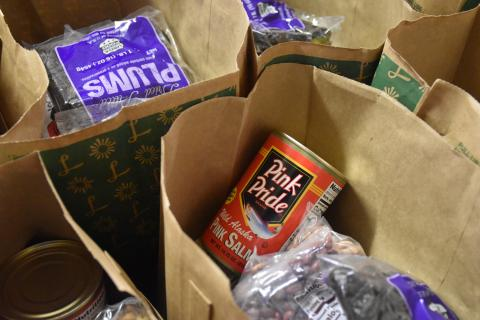[IMAGE DESCRIPTION: Brown paper grocery bags are filled with cans and fresh food.]