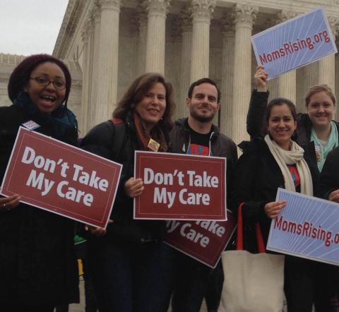 "A diverse group of people hold ""Don't Take My Care"" signs in front of the Supreme Court Building"