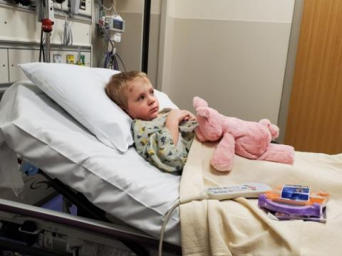 A young boy lays in a hospital bed holding a stuffed animal.