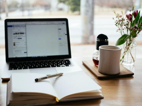[IMAGE DESCRIPTION: A photo of a laptop on a desk with an open journal and pen in front of it, a coffee mug out of focus behind it.]