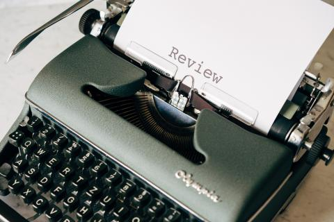 """photo of a typewriter with """"review"""" typed on the paper"""