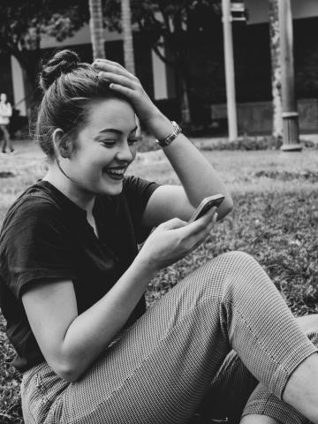 photo of a woman reading her mobile phone and laughing