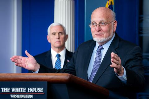 CDC Director Redfield speaks from a White House podium as VP Pence looks at him