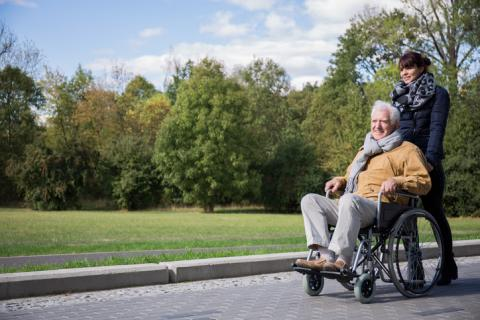 Person with white hair sits in wheelchair pushed by another person outdoors under a blue sky.