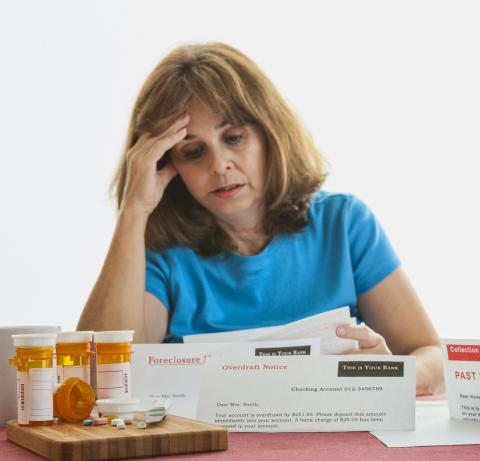 Woman looking at bills with prescription drugs sitting on a table
