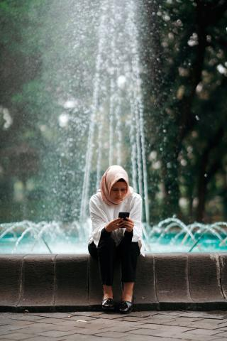 Photo of a woman sitting at an outdoor fountain, reading her phone