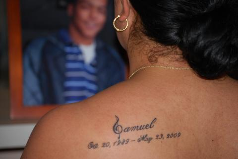 Isaida's back tattoo in memory of her son, Samuel. In the background is a framed photo of a smiling Samuel.