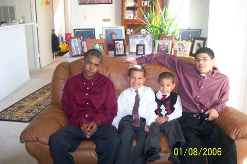 Isaida's four sons seated on a couch looking at the camera.