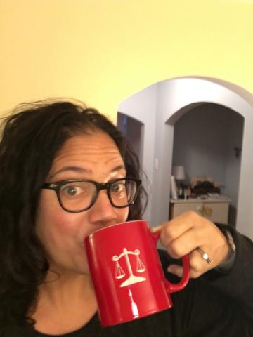 A woman drinking from a large red coffee mug