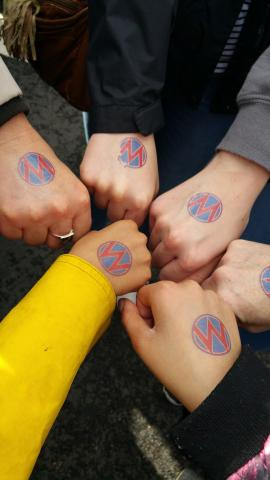 [IMAGE DESCRIPTION: A photograph of a circle of fists, kid-sized to adult, with MomsRising circle M tattoos.]