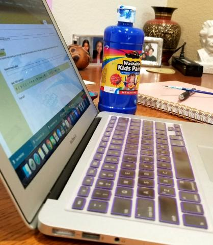[IMAGE DESCRIPTION: A photo of a laptop with a bottle of kids' paint, a paintbrush, a planner, and a pen in the background.]