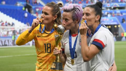 [IMAGE DESCRIPTION: Three players from the US Women's National Team for soccer smooch their medals and trophy.]