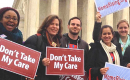 "A group of people hold ""Don't Take My Care"" signs standing in front of the U.S. Supreme Court"