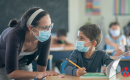 A teacher and student wearing a mask