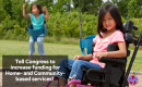 A girl with brown hair in a wheelchair sits smiling on a playground while her sibling swings