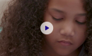 Child looking down with a play button overlayed.