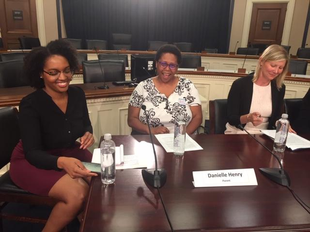 [IMAGE DESCRIPTION: Three women sit at a dark wooden table in Congress.]