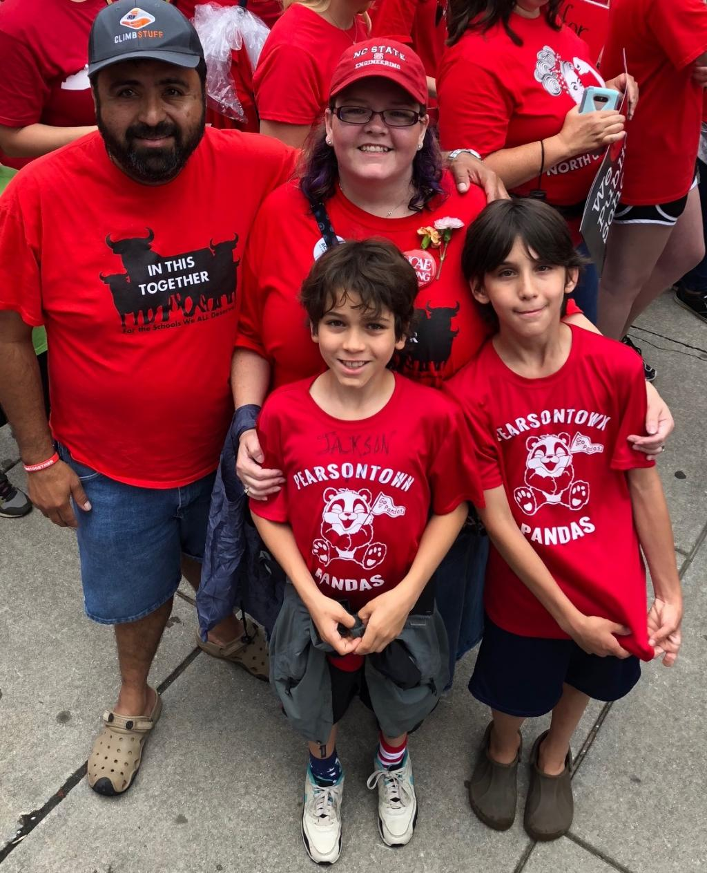 [IMAGE DESCRIPTION: A family of two adults, one with a beard, and two children, both with short dark hair, all wearing red shirts and smiles.]