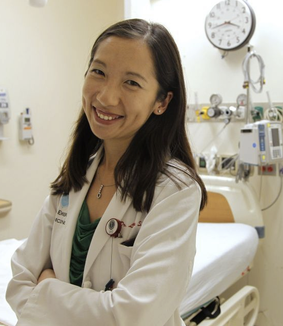 Person with long hair, wearing a white doctor's coat, smiles at the camera.
