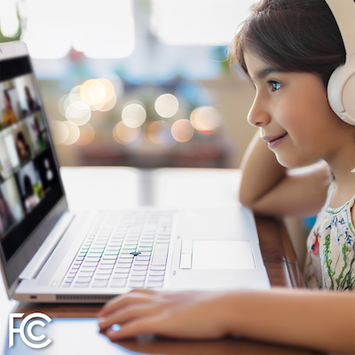 Girl with headphones looking at a computer (source: FCC)