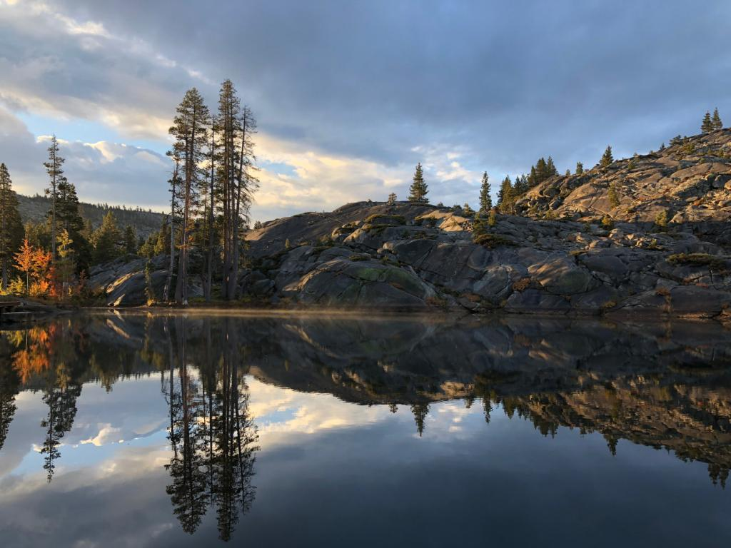 [IMAGE DESCRIPTION: A nature landscape photo featuring pines, granite outcroppings, and a serene pond reflecting the scenery.]