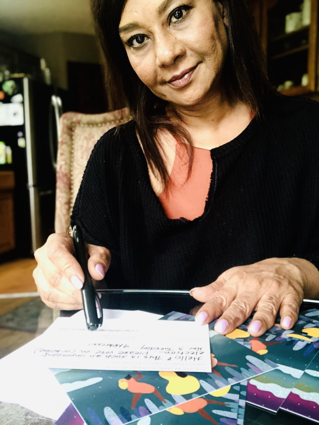 Photo of a MomsVote 2020 postcard volunteer filling out cards at her kitchen table