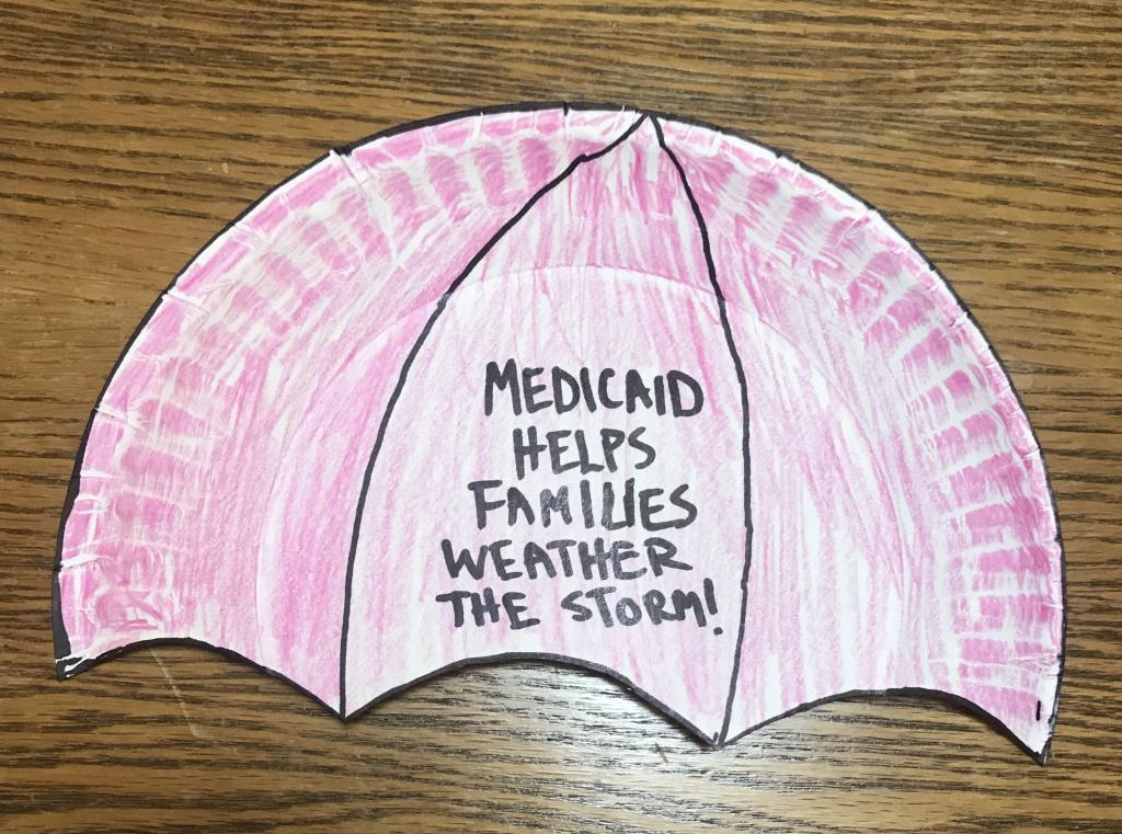 "red umbrella craft with ""Medicaid Helps Families Weather the Storm"""
