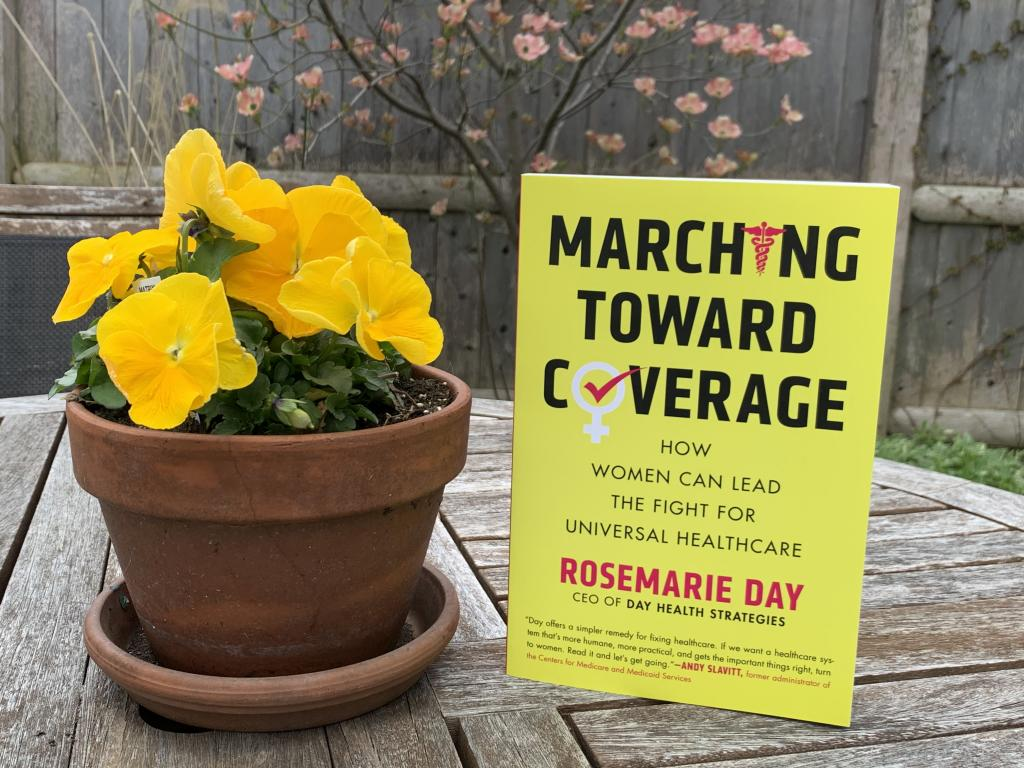 """[IMAGE DESCRIPTION: A photo of a table with a potted plant of yellow flowers and a book with a yellow cover and the title """"Marching Toward Coverage""""]"""