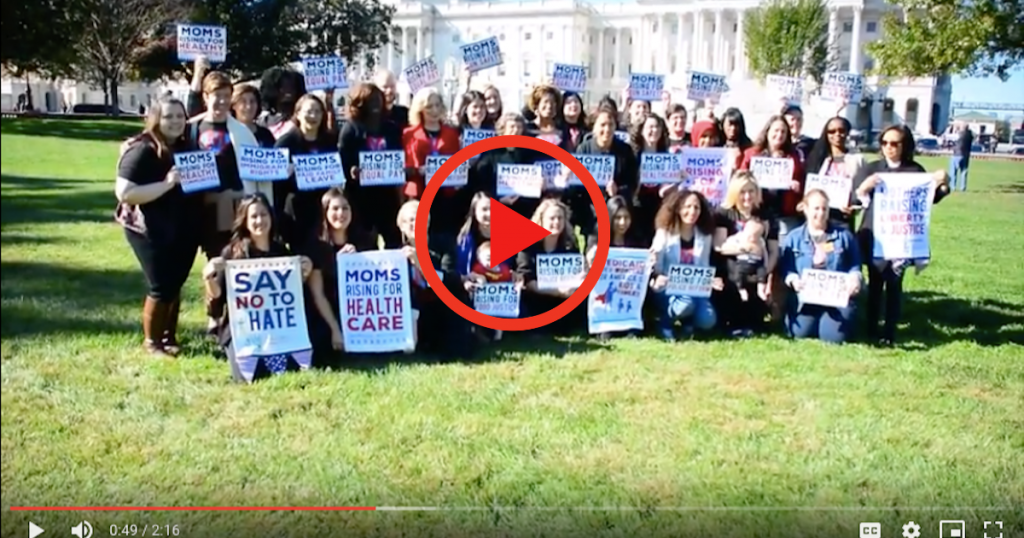 [IMAGE DESCRIPTION: A screenshot from a video with a group of people outside the US Capitol, holding MomsRising signs.]