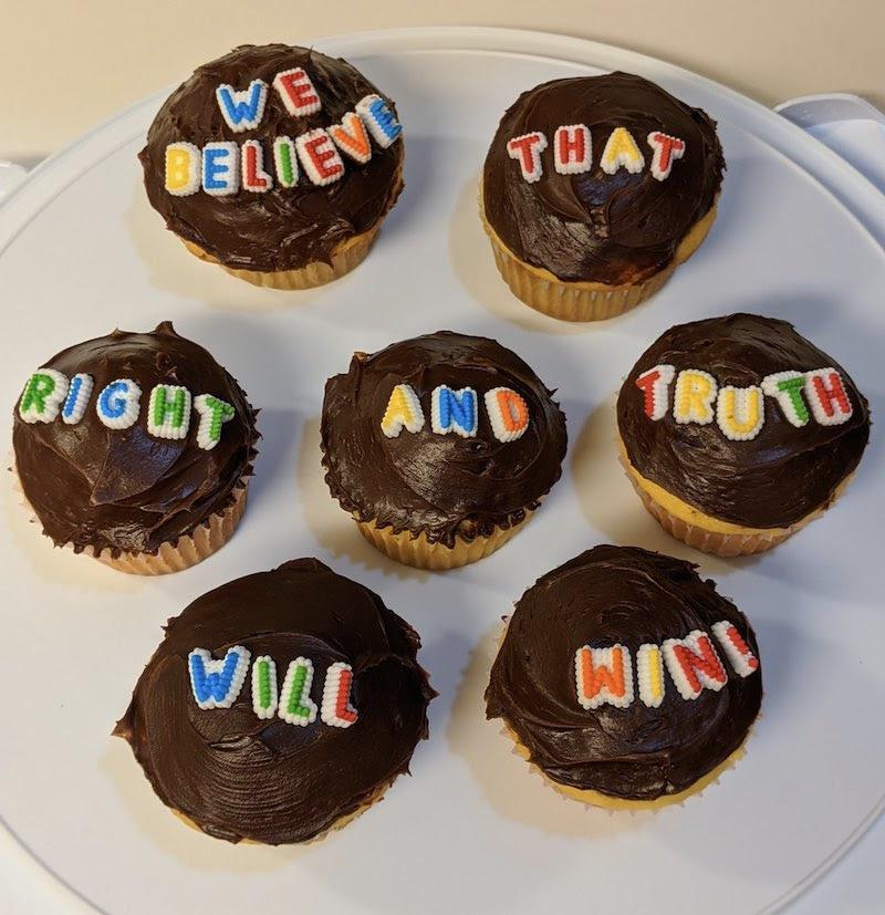 "[IMAGE DESCRIPTION: A photo of cupcakes with chocolate frosting and candy letters on top that read ""We believe that right and truth will win!""]"