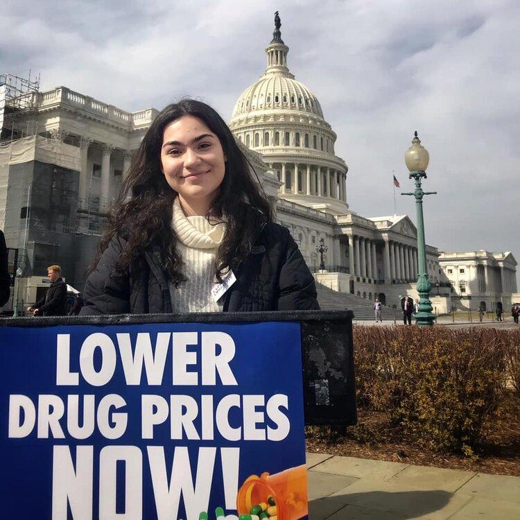 [IMAGE DESCRIPTION: A photo of a young woman with dark brown hair standing behind a poddium outside the US Capitol and smiling at the camera.]