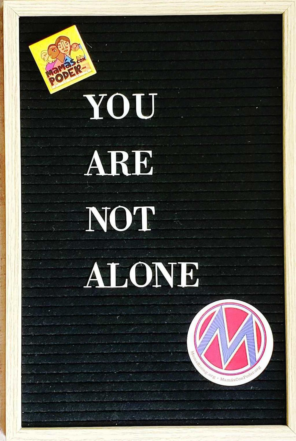 "[IMAGE DESCRIPTION: A photo of a letterboard with the words ""You are not alone"" on it.]"