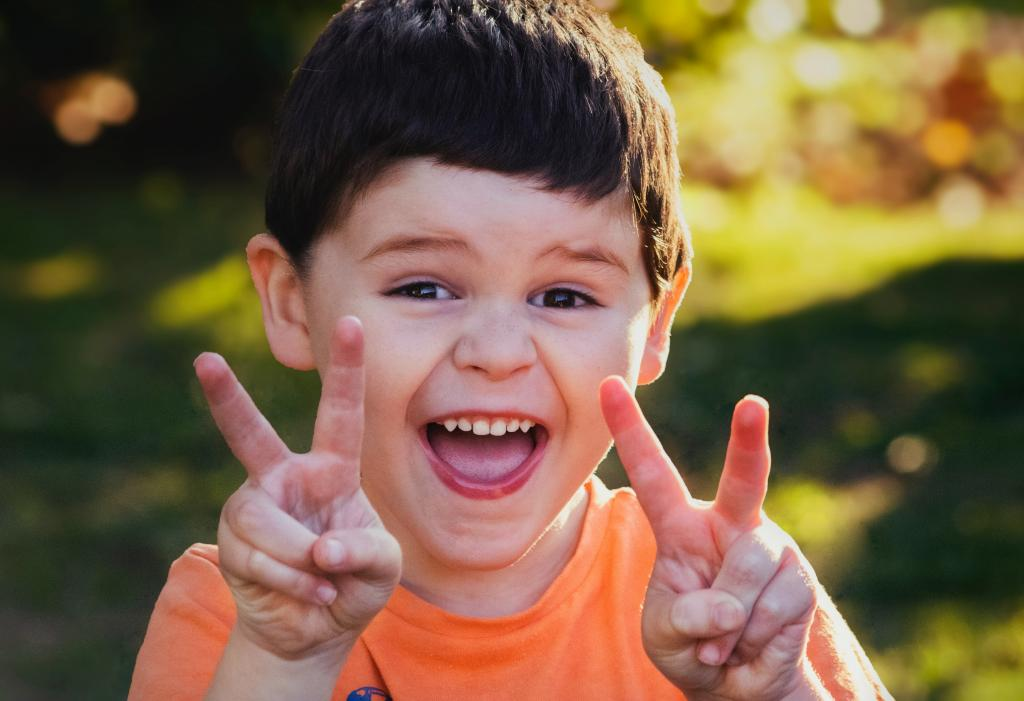 Photo of young child giving peace signs