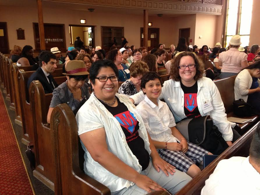 Two moms with son sitting in church pews