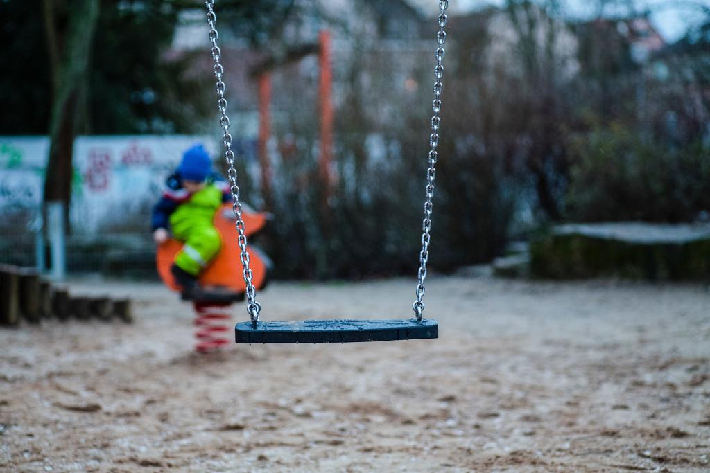 [IMAGE DESCRIPTION: A photo of an empty swing, with a child out of focus behind it.]