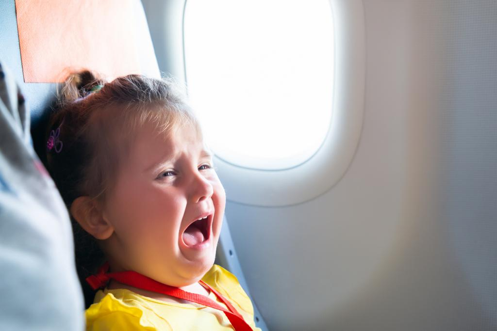[IMAGE DESCRIPTION: A photo of a young child with blond hair in a half ponytail crying in an airplane seat.]
