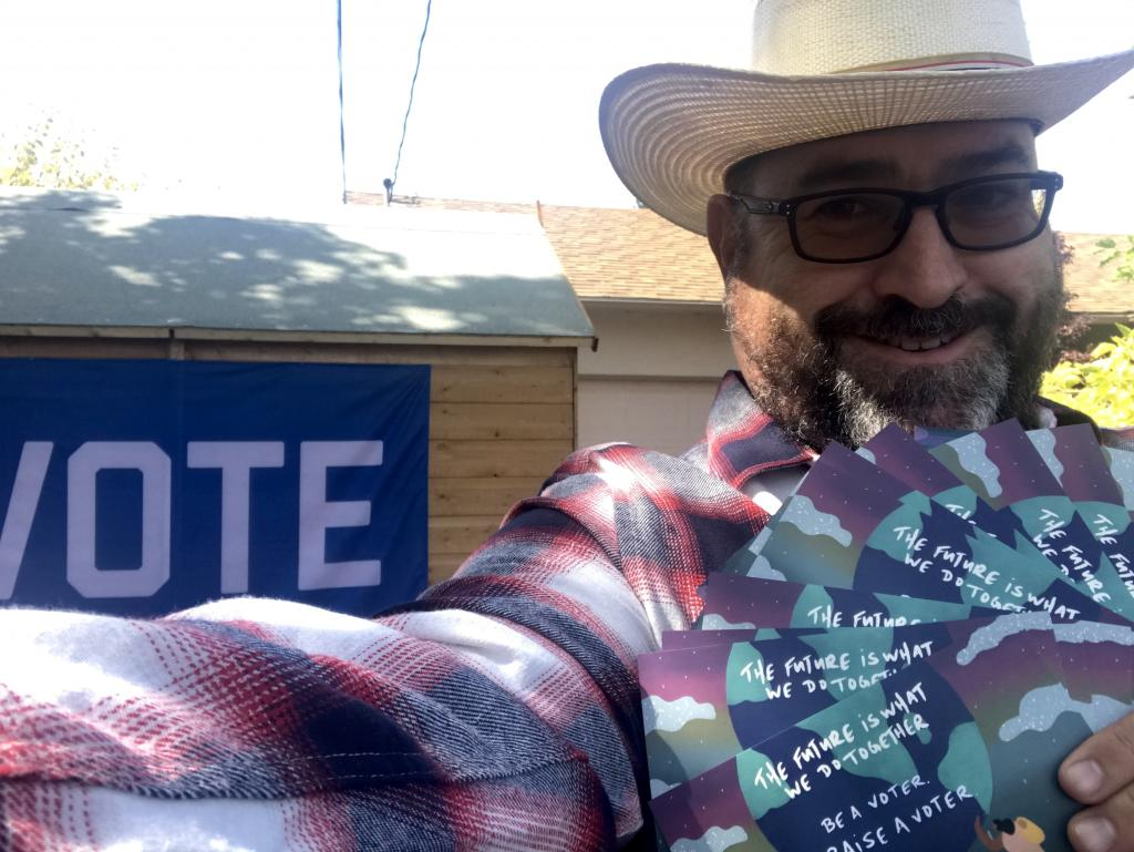 Photo of MomsVote volunteer with cowboy hat and vote sign