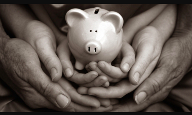 A black and white shot of a ceramic piggy bank in the hands of a young person, whose hands are held by an older set of hands.